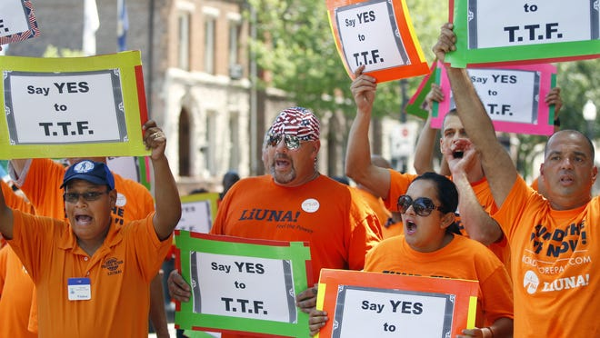 A large group of mostly construction workers hold signs and shout as they gather June 30 in front of the Statehouse in Trenton.