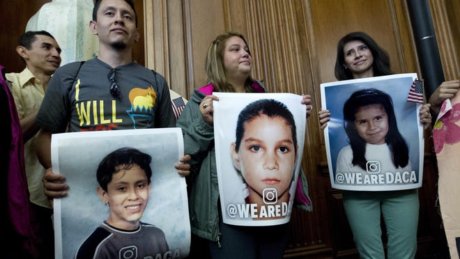 Dreamers from left; Isaac Montiel, 28, of NYC, Monica Camacho, 23, of Bethesda, Md., and Cynthia Toyco, 33, of Rogers, Arkansas, hold their pictures, during the House and Senate Democrats, news conference on Capitol Hill in Washington, Wednesday, Sept. 6, 2017. House and Senate Democrats gather to call for Congressional Republicans to stand up to President Trump's decision to terminate the Deferred Action for Childhood Arrivals (DACA) initiative by bringing the DREAM Act for a vote on the House and Senate Floor. ( AP Photo/Jose Luis Magan