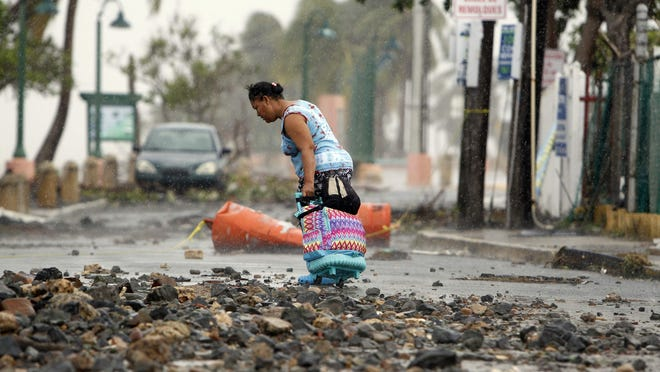 A woman pulls a travel case on a rock-scattered road in the aftermath of Hurricane Irma in Fajardo, Puerto Rico.