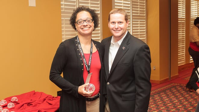 Former Lady Raiders basketball player Michelle Thomas, left, poses with Texas Tech athletics director Kirby Hocutt during a 20-year reunion for the 1993 national championship team. Thomas died Friday at age 47.