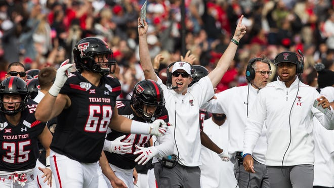 Texas Tech assistant coach Luke Wells, center, exults over a big play by the Red Raiders last season. On Saturday, Tech visits Iowa State, the program at which Wells had his first Big 12 job.