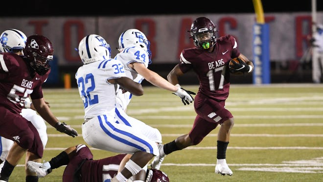 Bastrop sophomore Demire Thompson (17) looks for runnign room around the left side against rival Cedar Creek.