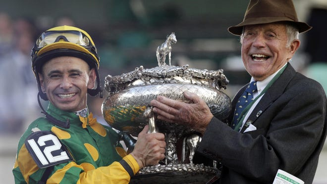 Jockey Mike Smith, left, and Cot Campbell, President of Dogwood Stables, hold the Belmont Stakes trophy in the winner's circle after Smith rode Palace Malice to win the Belmont Stakes horse race in Elmont, N.Y., Saturday, June 8, 2013.