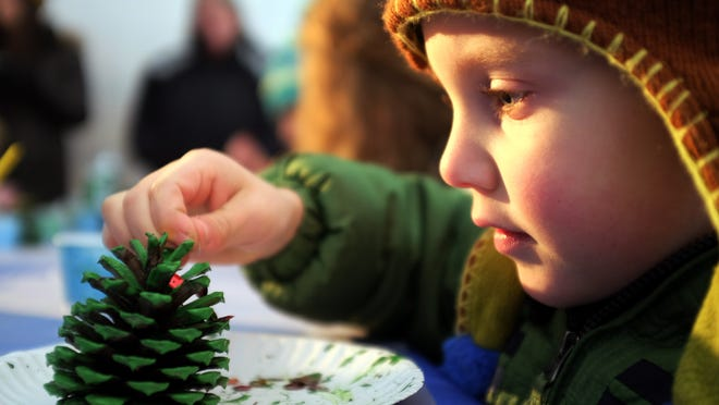 Noah Roberts, 4, of Dayton, Ohio, makes a pine cone Christmas tree ornament during the community get-together Saturday at Tuckerton Seaport.