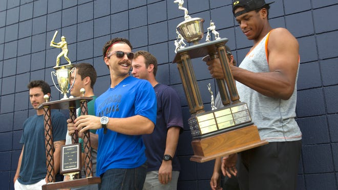Jason Kanzler, left, holding the FSL South Division trophy, smiles at Adam Brett Walker as he admires the shine on the FSL championship trophy  at the Lee County Sports Complex in Fort Myers Tuesday, September 9.