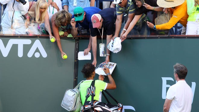 Rafael Nadal, of Spain, takes time to sign autograph before exiting Stadium 1 after losing to Canadian Milos Raonic in the men's quarterfinals at the BNP Paribas Open on Friday.