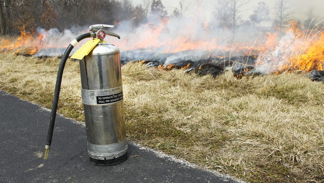 Fire extinguishers are kept close at hand during a prescribed burn.