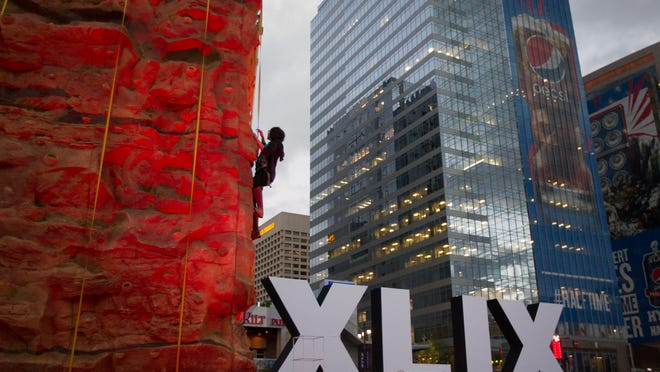 Republic reporter Caitlin McGlade climbs up the rock climbing wall at Super Bowl Central in Phoenix on Jan. 27, 2015.