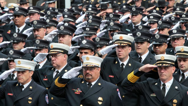 Thousands of law enforcement members salute as the hearse arrives during the funeral for Rochester Police Officer Daryl Pierson on Wednesday at the Blue Cross Arena in downtown Rochester.
