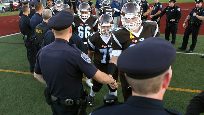 ER/Gananda players shake hands with law enforcement officers prior to Friday's game.