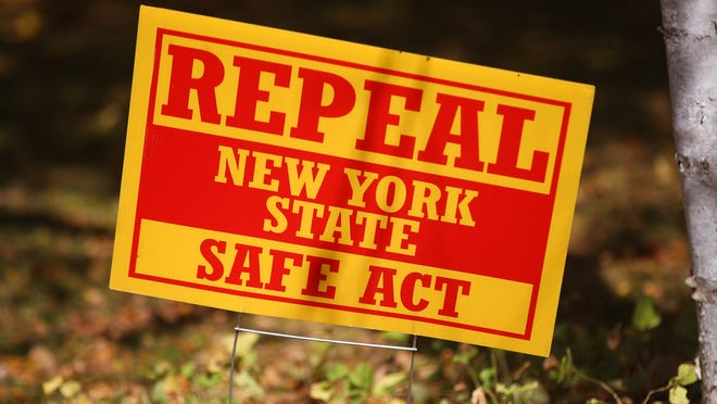 A sign urging the repeal of the SAFE Act is shown on a lawn in Perinton.