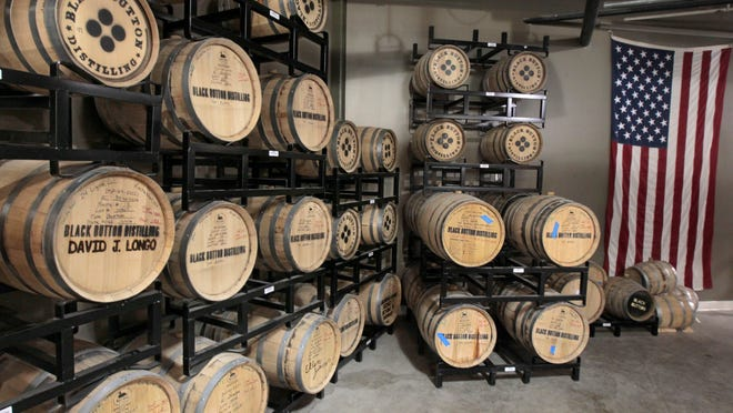 Barrels of finished bourbon ages on racks at Black Button Distilling on Railroad St.