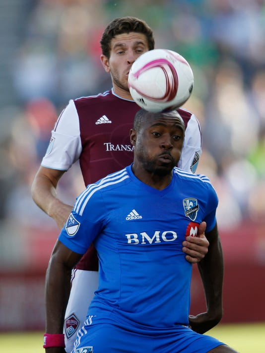 Montreal Impact's Nigel Reo-Coker, front, heads the ball in front of Colorado Rapids' Dillon Powers during the first half of an MLS soccer match in Commerce City, Colo., Saturday, Oct. 10, 2015. (AP Photo/David Zalubowski)
