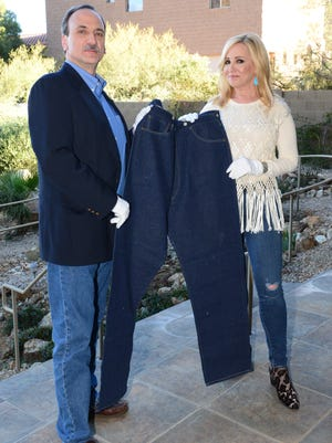 """Jamie Colby of Fox's """"Strange Inheritance"""" holds a pair 124-year-old blue jeans with Daniel Soules, an Americana appraiser and the owner of Daniel Buck Auctions."""