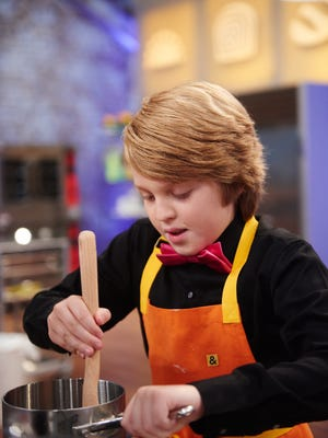 "Contestant Anthony Smith baking during the challenge ""Bake Sale"" as seen on Food Network's Kids Baking Competition, Season 1."