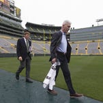 General manager Ted Thompson (right) and Mark Murphy, president and CEO, lead the board of directors onto the field Thursday for the shareholders meeting.