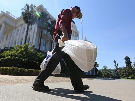 This file photo taken Tuesday, Aug. 12, 2014, plastic single-use bags are carried past the State Capitol in Sacramento, Calif.