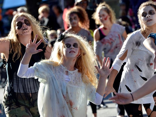 Zombies shamble through downtown York City during the 2014 Halloween parade.