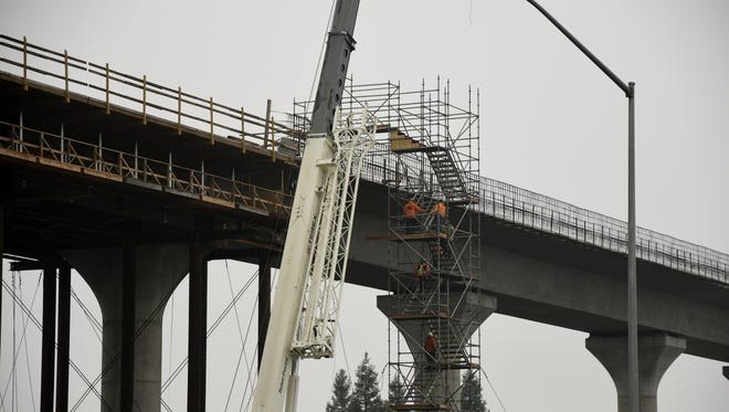 Construction workers climb to the top of the Central Valley segment of the California High Speed Rail located near the intersection of North and Cedar Avenues just outside of Fresno on Wednesday morning.