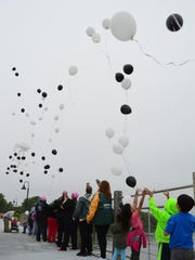 Community members release balloons on Saturday in memory of the victims of the May 3 Trestle Trail shooting in Menasha.