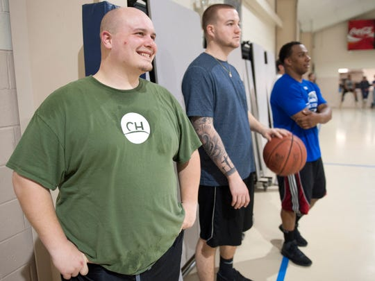 Calvary Hill Church Youth Pastor Joe O'Maley, left, stands on the sideline with Glassboro Police Officer Ryan Colone, center, and Glassboro Police Officer Craig Rawles as they watch a pickup basketball game at Calvary Hill Church in Glassboro on Monday. Members of the Glassboro Police started a department basketball team to connect with the community and take part in pickup games at the church on Monday nights.