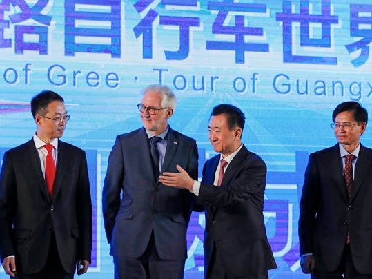Wanda Group Chairman Wang Jianlin, second right, shows the way to Union Cycliste Internationale (UCI) President Brian Cookson, second left, after they witnessed a signing ceremony for China to host a UCI world tour cycling race in Guangxi next year, at a hotel in Beijing, Thursday, Dec. 1, 2016. (AP Photo/Andy Wong)