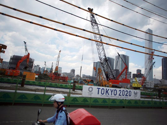 FILE - In this June 2, 2017, file photo, a postman rides a motorcycle past the construction site of the athlete's village for the 2020 Tokyo Summer Olympics at Tokyo's Harumi. Tokyo Gov. Yurkio Koike explained on Friday, Jan. 26, 2018, the city will more than double the billions it is already budgeting to stage the Games. However, the International Olympic Committee and Tokyo organizers say the city's added costs are for many projects that would have been done - with our without the Olympics. (AP Photo/Eugene Hoshiko, File)