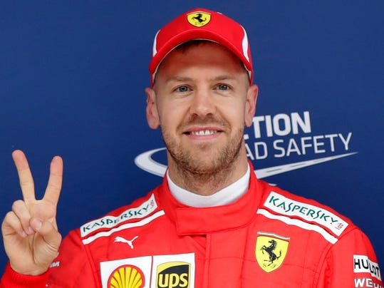Ferrari driver Sebastian Vettel of Germany flashes a v-sign after taking pole position for the Chinese Formula One Grand Prix at the Shanghai International Circuit in Shanghai, Saturday, April 14, 2018. (AP Photo/Andy Wong)