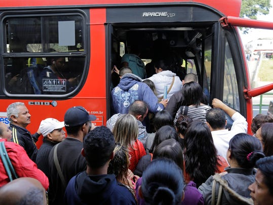 People crowd on to a bus outside the Arthur Alvim metro station during a metro strike in Sao Paulo, Brazil, Thursday, June 5, 2014. This city that will host the World Cup opening match in a week was thrown into transit chaos Thursday as subway and overland commuter train operators went on strike, putting at risk the only means that most soccer fans will have to reach the stadium. (AP Photo/Nelson Antoine)