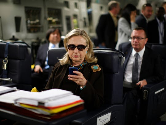Then-Secretary of State Hillary Rodham Clinton checks her Blackberry from a desk inside a C-17 military plane upon her departure from Malta, in the Mediterranean Sea, bound for Tripoli, Libya, in October, 2011. Clinton used a personal email account during her time as secretary of state, rather than a government-issued email address, potentially hampering efforts to archive official government documents required by law.