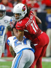 Arizona Cardinals wide receiver Larry Fitzgerald (11) takes a hit from Detroit Lions free safety Glover Quin (27) in the second quarter of their NFL game on Sunday, Nov. 16, 2014, in Glendale, Ariz.  Fitzgerald left the field after the play.