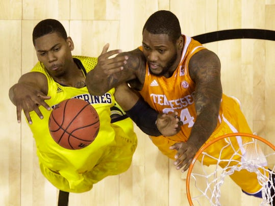 Michigan's Glenn Robinson III and Tennessee's Jeronne Maymon (34) go after a rebound during the first half of an NCAA Midwest Regional semifinal college basketball tournament game Friday, March 28, 2014, in Indianapolis. (AP Photo/David J. Phillip)