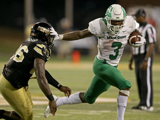 North Texas running back Jeffery Wilson (3) is defended by Southern Miss linebacker Jeremy Sangster (26) in the second half Saturday at M. M. Roberts Stadium. North Texas won 43-28.