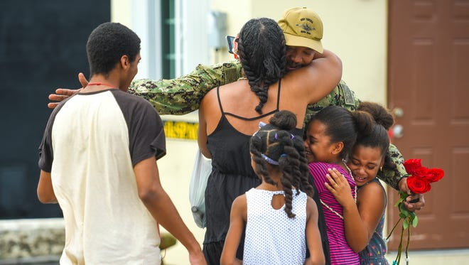 Navy Chief Trey Wheeler gets a group hug from his family after returning aboard the Los Angeles-class attack submarine U.S.S. Topeka, at Polaris Point in Piti on March 30, 2018. The vessel and its crew had just returned to their homeport at Navy Base Guam, after a three-month deployment in the Western Pacific.