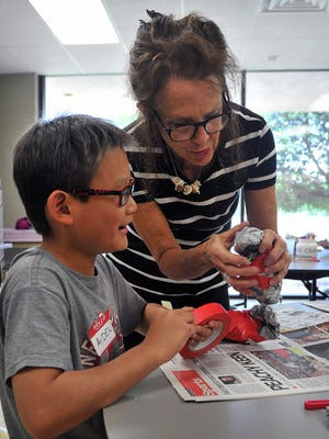 Aiden Ok gets some guidance on how to shape the body of the art bird he and other children are creating at the Wichita Falls Museum of Art at Midwestern State University's Art Camp Monday.