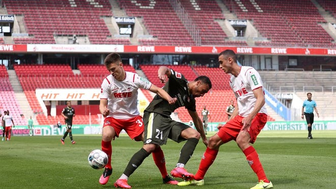 Karim Onisiwo, center, of FSV Mainz 05 is challenged by Cologne's Noah Katterbach during the German Bundesliga soccer match between 1. FC Cologne and FSV Mainz 05 in Cologne, Germany, Sunday, May 17, 2020. The German Bundesliga becomes the world's first major soccer league to resume after a two-month suspension because of the coronavirus pandemic.