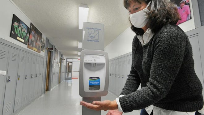 Weymouth Elder Services director, Karen Johnston, demonstrates a hand sanitizing station in the corridor at the senior center.