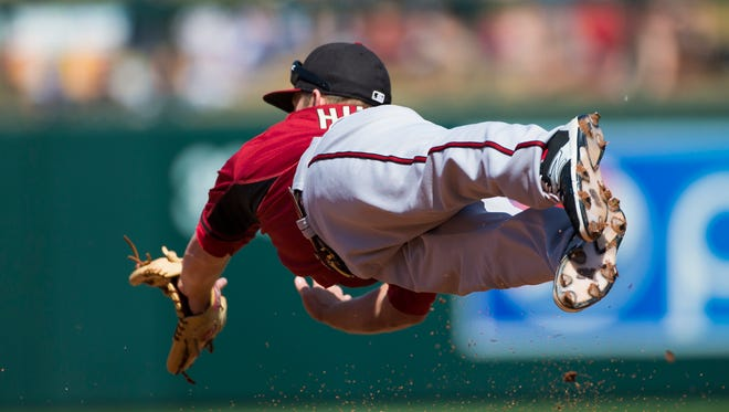 Arizona Diamondbacks second baseman Aaron Hill dives for a ball hit by Colorado Rockies Justin Morneau during spring training action at Salt River Fields at Talking Stick March 29, 2015.