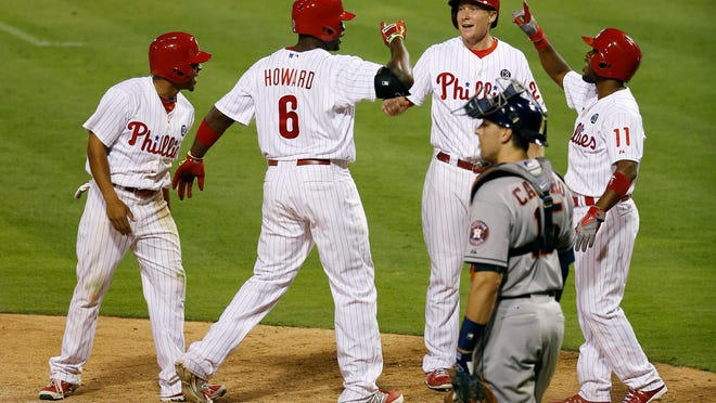 From left: The Phillies' Ben Revere, Ryan Howard, Cody Asche and Jimmy Rollins celebrate near Houston Astros catcher Jason Castro after Howard's grand slam during the eighth inning Thursday in Philadelphia. The Phillies won 6-5.