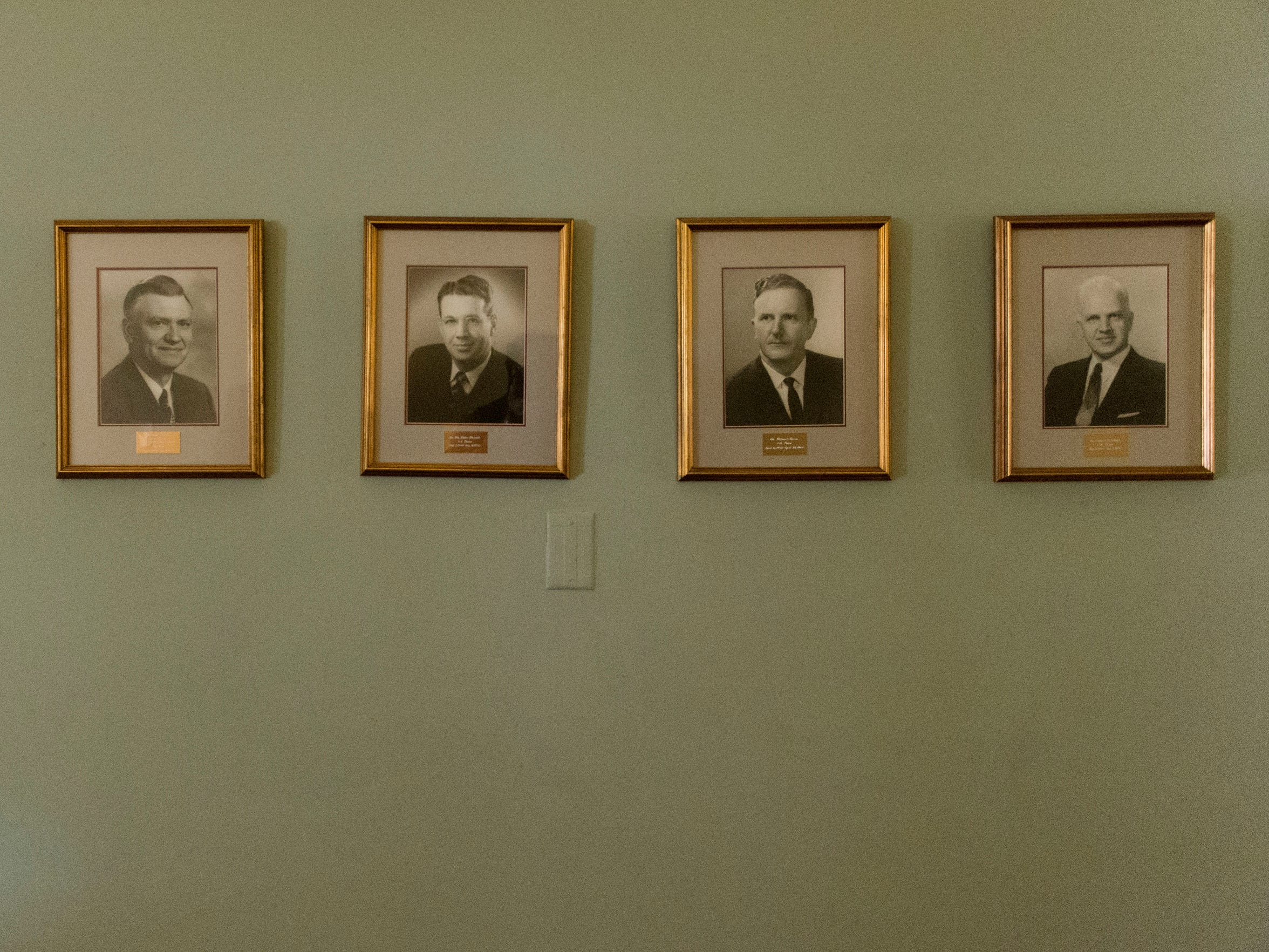 Former pastors of Fifth Ave. Baptist Church line a hallway in the church.