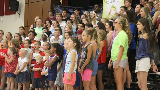 "Students of all ages ready their voices in the cafeteria of Harding High School on Tuesday. They were there to sing ""It's a Small World (After All),"" with the hopes that educators across the country will encourage their students to do the same."