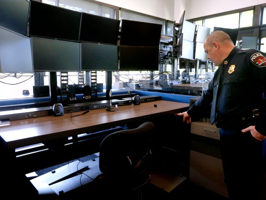 Murfreesboro Police Chief Mike Bowen shows off the adjustable desks for dispatchers at the new Murfreesboro Police Headquarters during a tour on Monday.