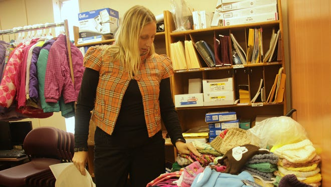 United Way of Otero County Director of Marketing and Public Relations Michelle Brideaux sorts through donated warm hats and scarves for their annual Koats for Kids program.