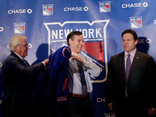 The New York Rangers new head coach David Quinn, center, puts on a team jacket while team president Glen Sather, left, and general manager Jeff Gorton look on during an NHL hockey news conference in New York, Thursday, May 24, 2018.