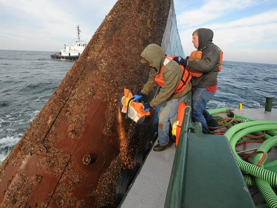 Workers cut a hole into the Shearwater, releasing trapped