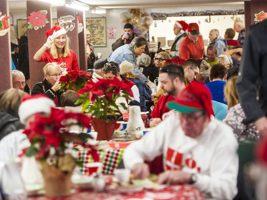 Servers raise fingers to say how many seats are available during the Danny Berg Memorial Dinner at the Great Falls Senior Center on Friday.