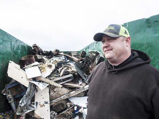 """Montana Department of Natural Resources and Conservation land manager Andy Burgoyne stands in front of a dumpster full of trash from a dump site on DNRC recreational land Tuesday. """"We want people to use land where it's legally accessible but with that comes respect. This kind of abuse is damaging and costly,"""" Burgoyne said."""
