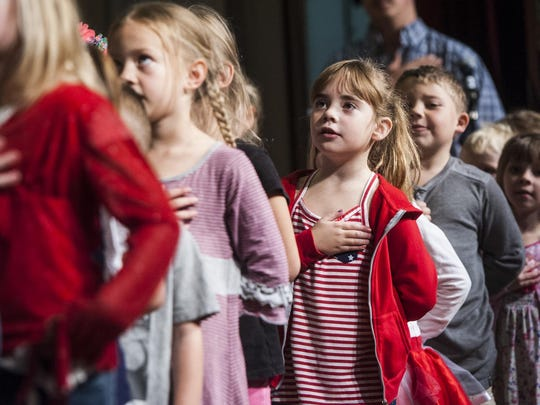 Students recite the Pledge of Allegiance during the