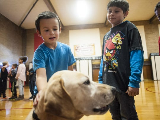 Jaxon Jones, a third-grade student at Roosevelt Elementary, pets Marshall the Miracle Dog during an assembly Thursday.