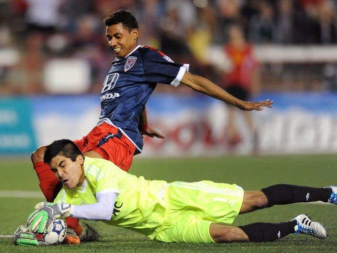 Indy Eleven midfielder Kleberson and Carolina RailHawks goalkeeper Akira Fitzgerald go after a ball as it gets into the box late in the game at Carroll Stadium, Saturday, April 12, 2014, in Indianapolis.